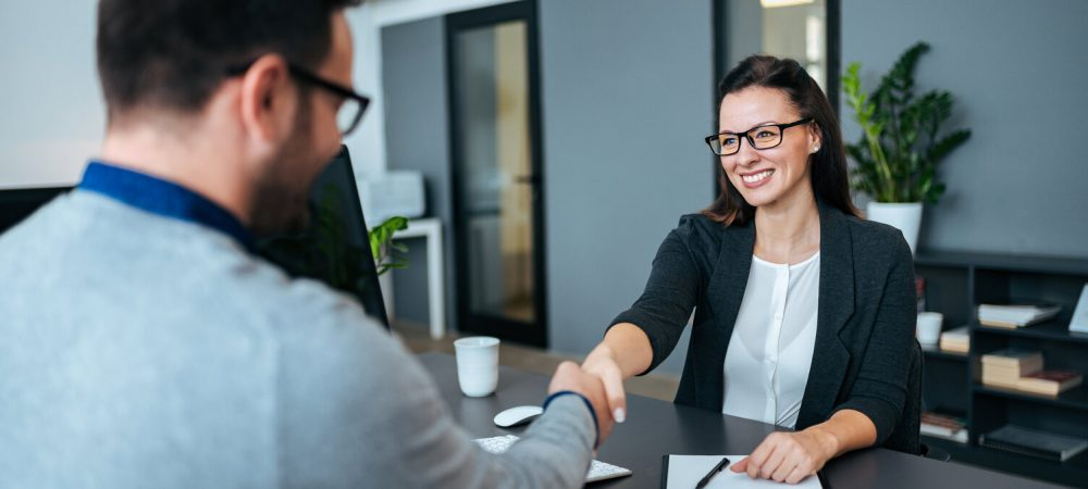 Businesswoman and businessman shaking hands in modern office.